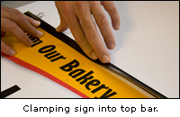 Clamping sign into top bar